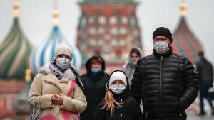 En kvinna, en flicka och en man poserar framför en färggrann katedral i Moskva. Personerna har varma ytterkläder på sig och alla tre bär munskydd.