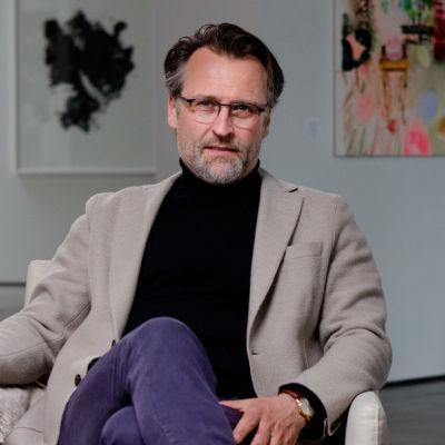 Jan Söderblom sitter med benen i kors i en beige fåtölj. Färggranna tavlor hänger på väggarna i bakgrunden.