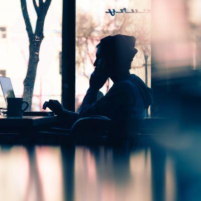 En man sitter vid en dator och hans bild speglas i det närmaste bordets yta.