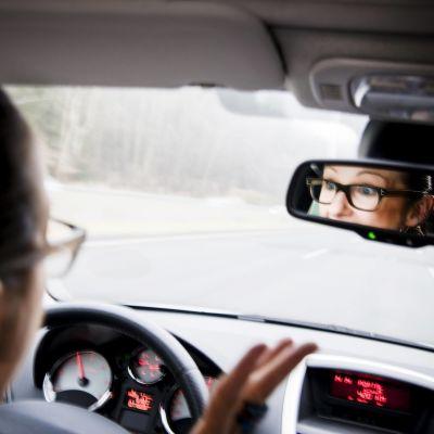 En kvinna slår ut med händerna vid ratten i en bil. Hon ser ilsken ut i backspegeln.