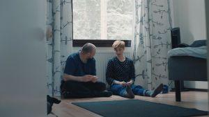 Syskonen Veera och Ville sitter på golvet och pratar i dokumentären Veeras magiska liv.