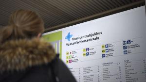 en infoskylt över Vasa Centralsjukhus med en kvinna i förgrunden
