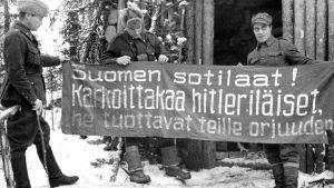 """Lapin sota. Kapteeni, luutnantti ja sotamies esittelevät levitettyä banderollia, jossa on Neuvostoliiton Suomeen lähettämää saksanvastaista sotapropagandaa. Banderollissa teksti """"Suomen sotilaat ! Karkoittakaa hitleriläiset he tuottavat teille orjuuden""""."""