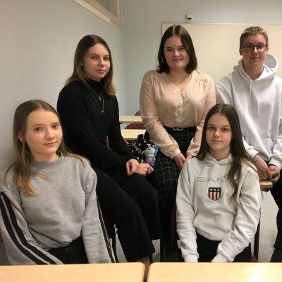 Kuusi ysiluokkalaista istuu luokassa.
