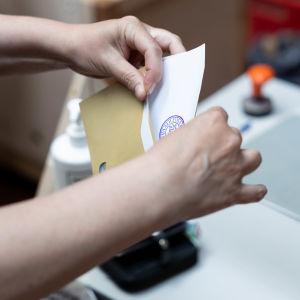 Närbild på händer som lägger röstsedel i ett brunt kuvert.