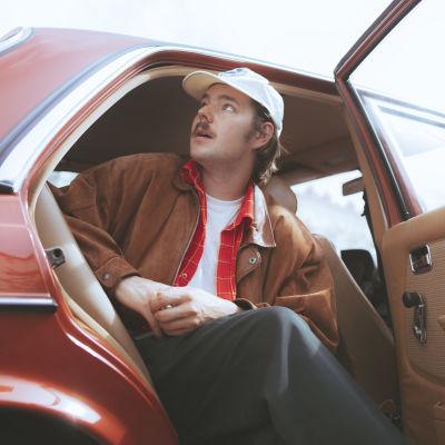 Artisti Arppa istuu punaisen autonsa takapenkillä Helsingin Kalliossa.