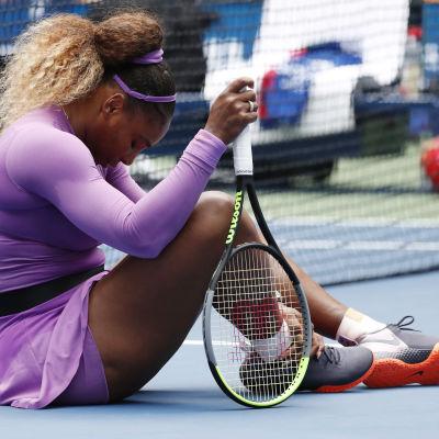 Serena Williams sitter på planen och håller om sin vrist.