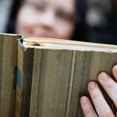 En gammal bok hålls i med en hand.