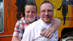 Michael Björklund och Lars Forsman poserar framför cateringbussen.