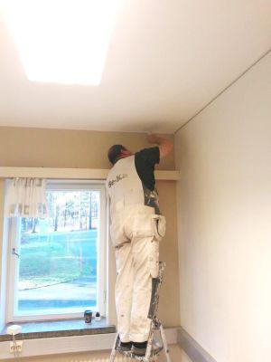 Man i byggföretaget Se-Kas vita overall målar innervägg.
