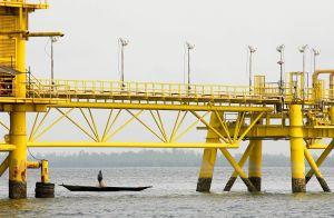 Nigeriansk fiskare i träbåt under pipeline