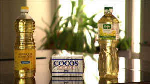 Auringonkukkaöljy, kookosrasva ja rypsiöljy pöydällä