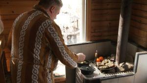 Kokki Janne Pekkala tekee ruokaa saunan kiukaalla
