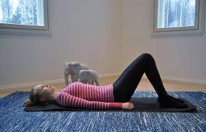 Nainen tekee pilatesliikettä matolla