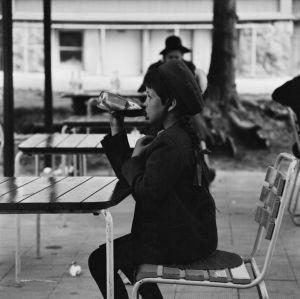 Tyttö juo limonadia ulkona kahvilan pöydän ääressä 1966.