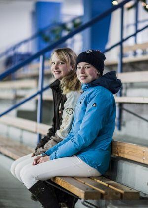 kaksi nuorta naista istumassa katsomossa