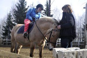 Ratsukko kentällä, hoitaja pitää ponia otsatukasta kiinni
