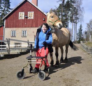 Tyttö kävelee rollaattorin kanssa, hevonen seuraa
