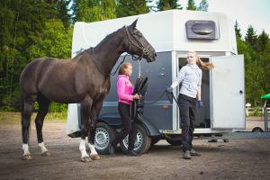 hevonen ja kaksi naista trailerin edessä