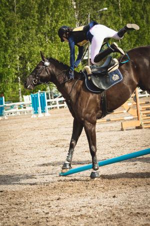 Ratsastaja putoamassa hevosen selästä