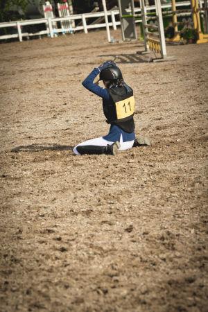 hevosen selästä pudonnut ratsastaja istuu kentällä