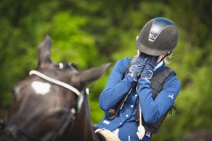 pettynyt ratsastaja hevosen selässä kädet kasvoillaan