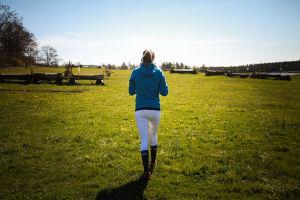 Ratsastaja kävelee nurmikentällä