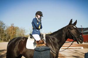 Ratsastaja niistää hevosen selässä, hoitaja seisoo vierellä
