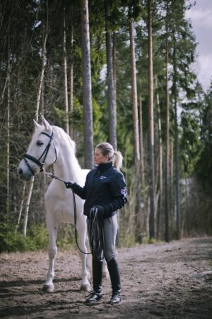 Hevonen ja juoksuttaja metsätiellä