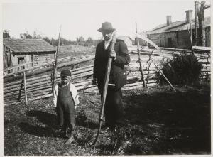Mies ja poika maatilan pihalla 1900-luvun alussa, miehellä sirppi kädessä ja viikate olalla