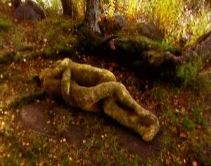 Olavi Lanun veistos kuvaa syleilyä metsän siimessä.