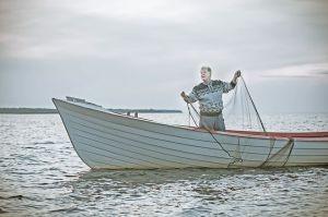 Mies veneessä nostamassa verkkoa