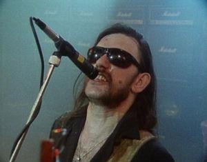 Basisti-laulaja Lemmy laulaa Eat the Rich -musiikkivideolla.
