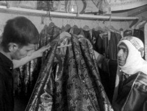Kangaskauppias esittelee damastista tehtyä vaatetta