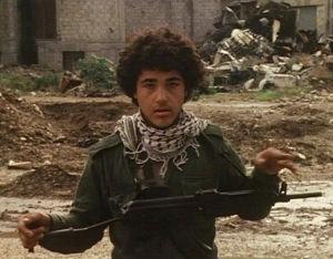 Nuori poika partioimassa aseen kanssa kadulla Tripolissa Libyassa