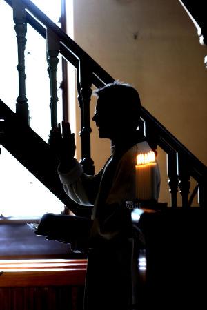 pappi kantaa kynttelikköä portaissa