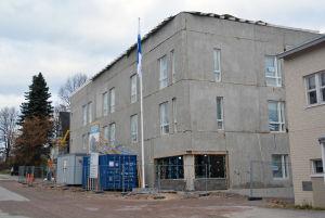 Ett hus som ännu är halvfärdigt med en flaggstång utanför med flaggan i topp.
