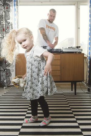 Tytär tanssi etualalla, isä soittaa dj-laitteilla taka-alalla.