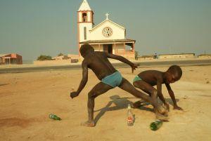 Kaksi angolalaispoikaa pelaavat jalkapalloa lasipullolla. Taustalla vaalea kirkko.