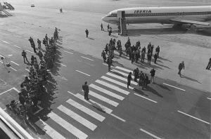 Ulkomaisen vieraan vastaanotto: presidentti Urho Kekkonen kävelee vieraineen kohti lentoasemaa, ympärillä parveilee valokuvaajia, valokuvaajien rivi köyden takana.