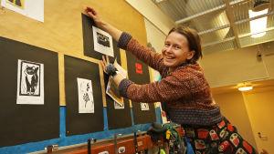 opettaja ripustaa kuvia seinälle