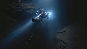 Sukeltaja sukeltaa pimeässä luolassa, valokeila tulee takaa.