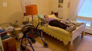 Äldre kvinnan Hilkka Jämsä ligger i en säng med rollator bredvid sig.