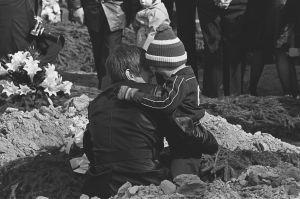 Lapuan patruunatehtaan räjähdysonnettomuuden uhrien hautajaiset 24.4.1976. Surevia omaisia haudalla.