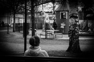 Kvinna på parkbänk tittar på lekande barn