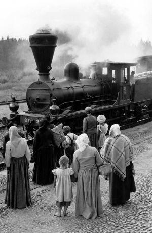 Ihmisiä ja höyryveturi, joka saapuu asemalle.