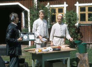 Yleisradio studio-ohjaaja Kalevi Riutta työssä. Jaakko Kolmonen ja Veijo Vanamo valmistavat ruokaa.  (1977)