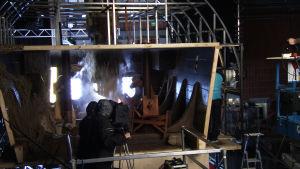 Ylen studiossa kuvataan keskiaikaisen laivan hyttilavastetta, jonka läpi iskeytyy laivan masto.