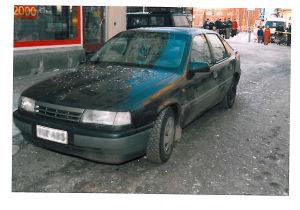 En svart bil med söndriga rutor. Människor som tittar på i bakgrunden.