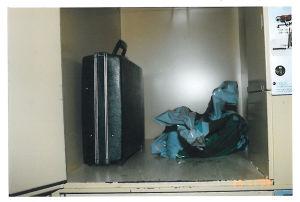 Inne i förvaringsboxen finns en svart portfölj och en plastpåse.